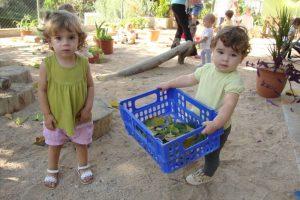 Dues nenes carreguen fulles seques en una caixa