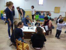 Un grup de pares i mares amb els seus fills pinten castenyes