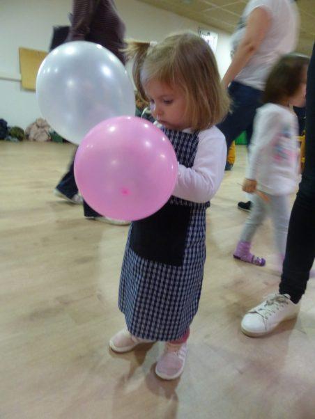 Una nena juga amb el davantal de castanyera ama un globus a la ma