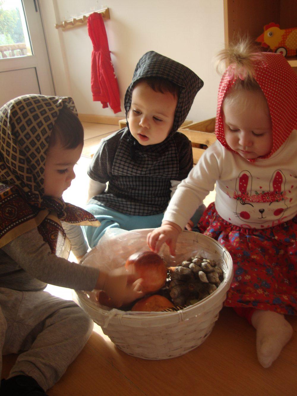 Tres infants amb mocadors al cap jugant amb la panera de la tardor