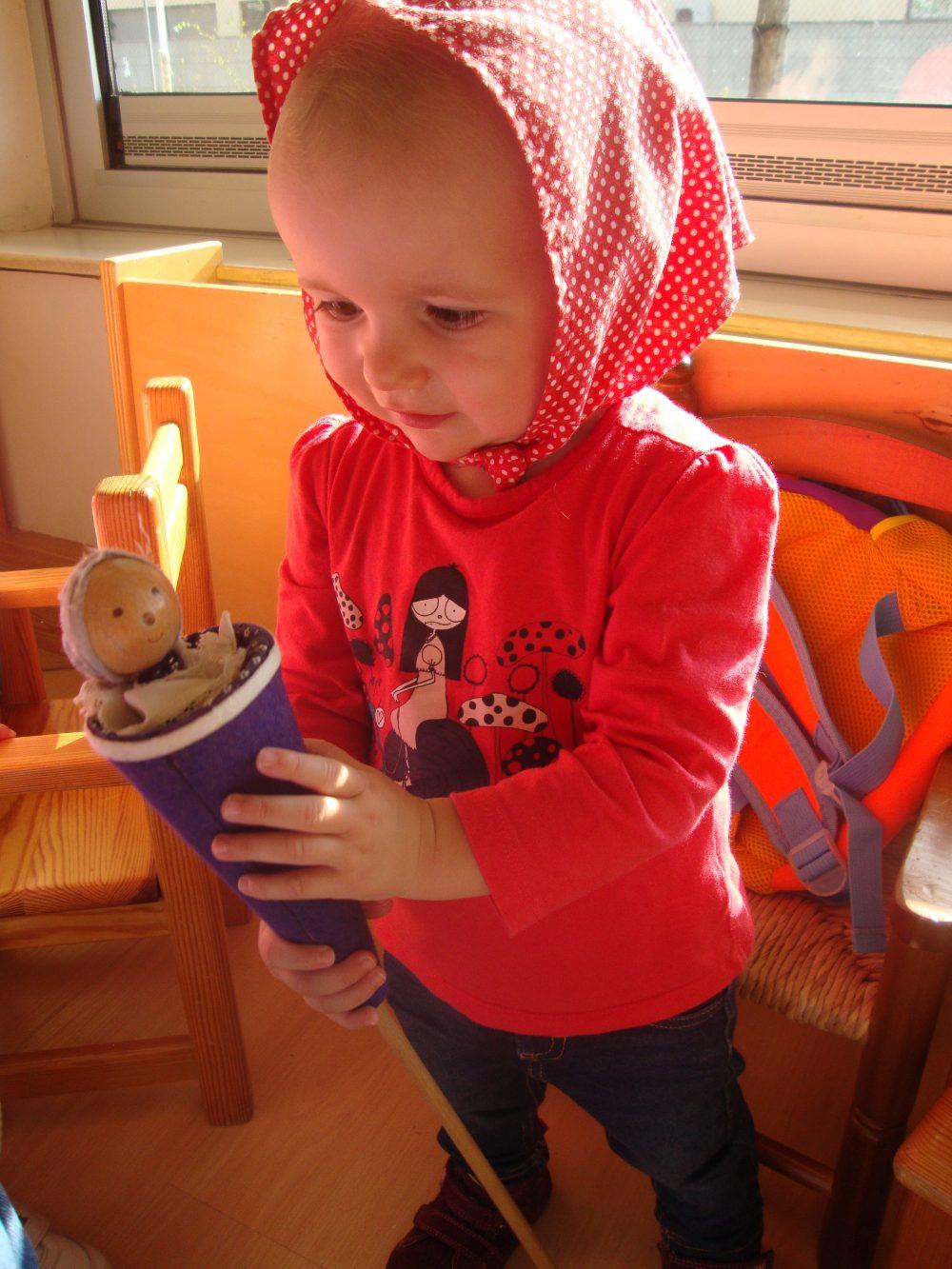 Una nena amb el mocador de castanyera al cap i el titella a les mans