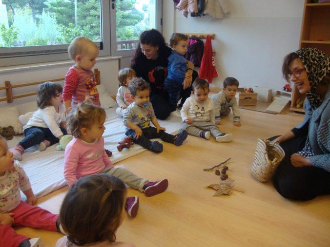 La Castanyera asseguda al terra amb els infants al voltant ens mostra castanyes i fulles de tardor