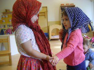 dues nens es donen la mà vestides de castanyera