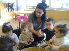 la mestra i un grup de nens miren que hi ha dins la panera de la tardor