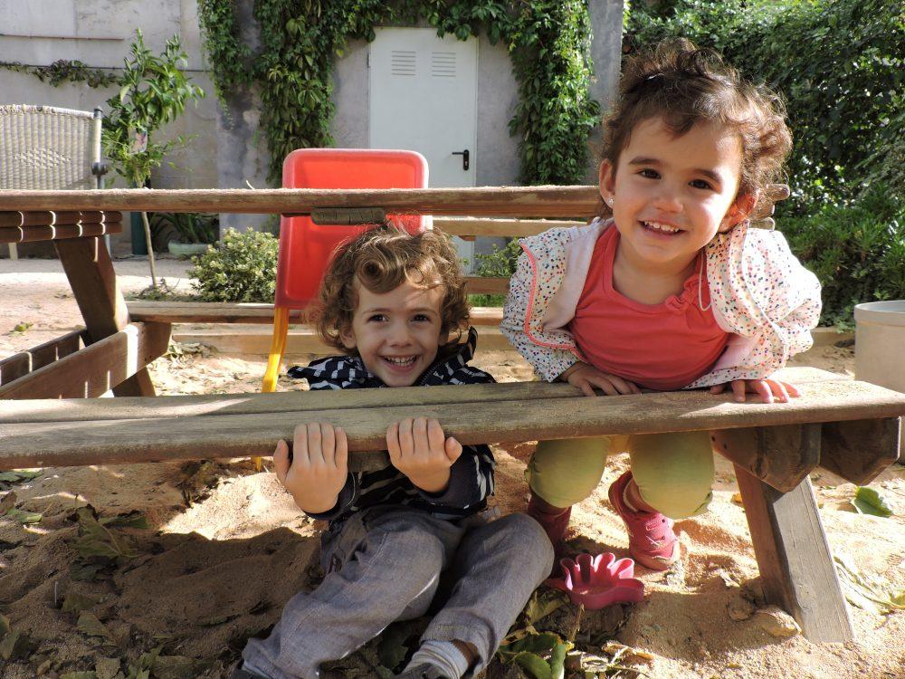 un nen i una nena amagats a sota una taula i riuen