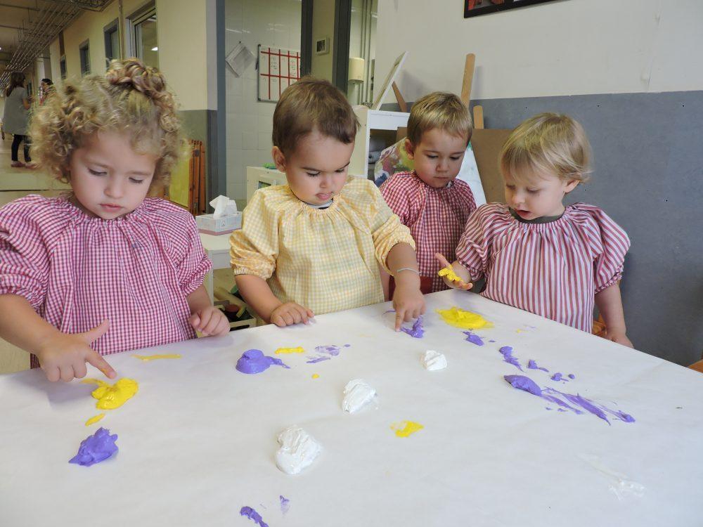 Quatre infants comencen a tocar amb els dits la pintura blanca, lila i groga que hi ha sobre la taula folrada.
