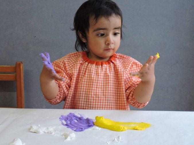 Una nena s´embruta les mans de pintura, i després se les mira.