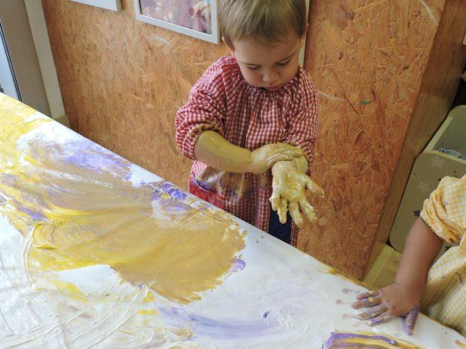 Un nen, després de pintar sobre la taula, s'extén la pintura per les mans i l'avantbraç.