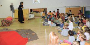 Grup d'infants de dos anys observant amb atenció com es vesteix la Maria Castanyera