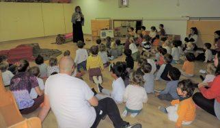Una sala amb un grup nombrós d'infants de dos anys que mirant com la Maria Castanyera els narra una història