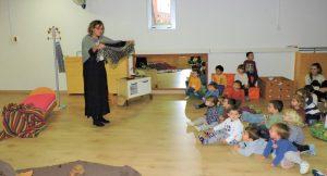 La Maria Castanyera està ensenyant a un grup d'infants de dos anys el mocador que es posarà al cap.