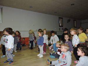 Grup d'infants alguns drets ballant i altres asseguts al terra