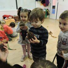 Nens olorant pinyes i elements de la tardor