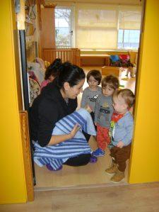 els infants toben el tió a la porta