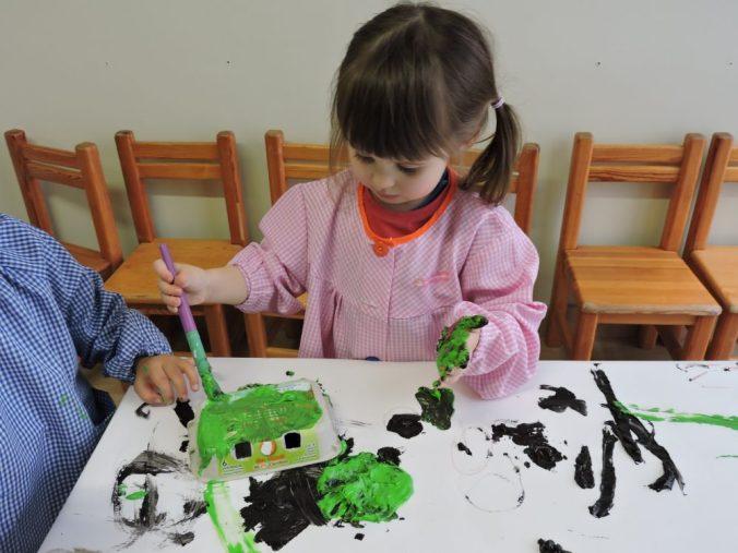 Una nena pinta una ouera mentre té l'altra mà plena de pintura verda.