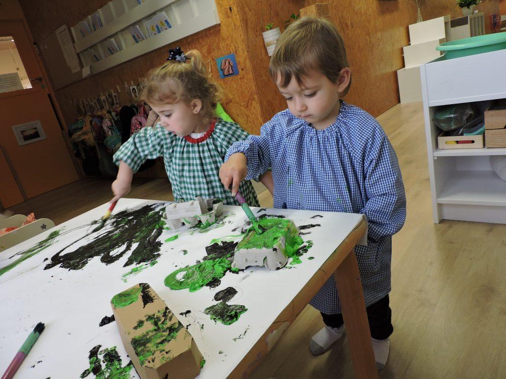 Un nen i una nena pinten oueres sobre la taula.