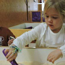 Una nena amb una pinza de color lila a la mà posant una càpsula a un recipient
