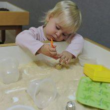 Una nena amb una cullera a la mà tocant pa rallat