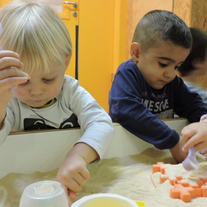 Dos nens manipulant pa rallat amb culleres