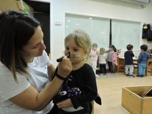 Educadora pintant la cara de conill a una nena