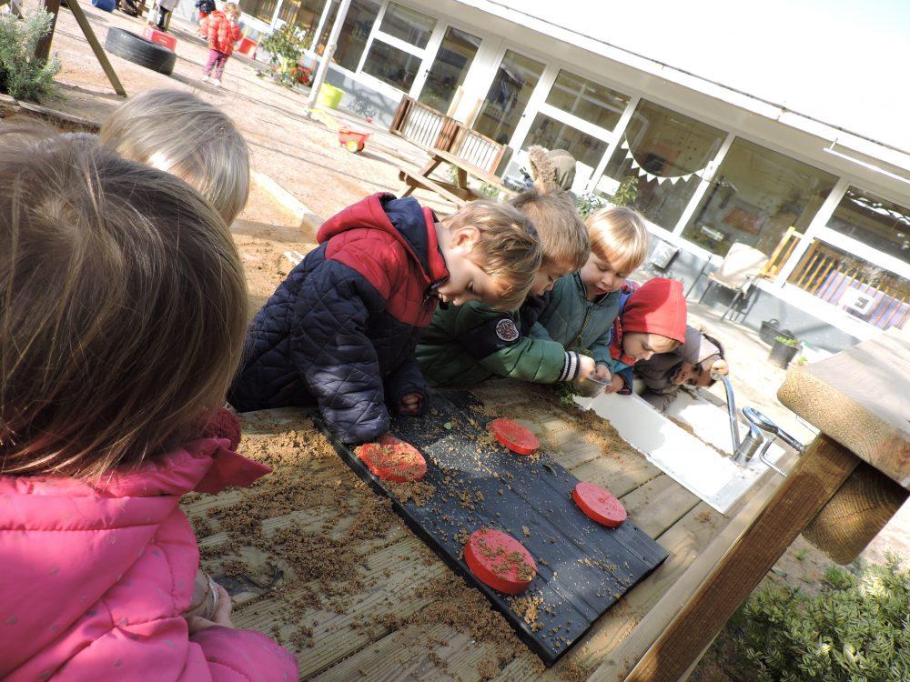 Infants juguen a la cuineta del pati.