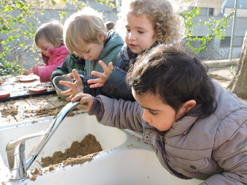Una nena es mira l'aixeta de la cuina del pati mentre altres infants juguen al seu costat.