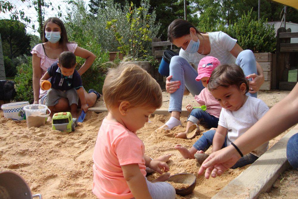 infants i famílies jugant al jardí