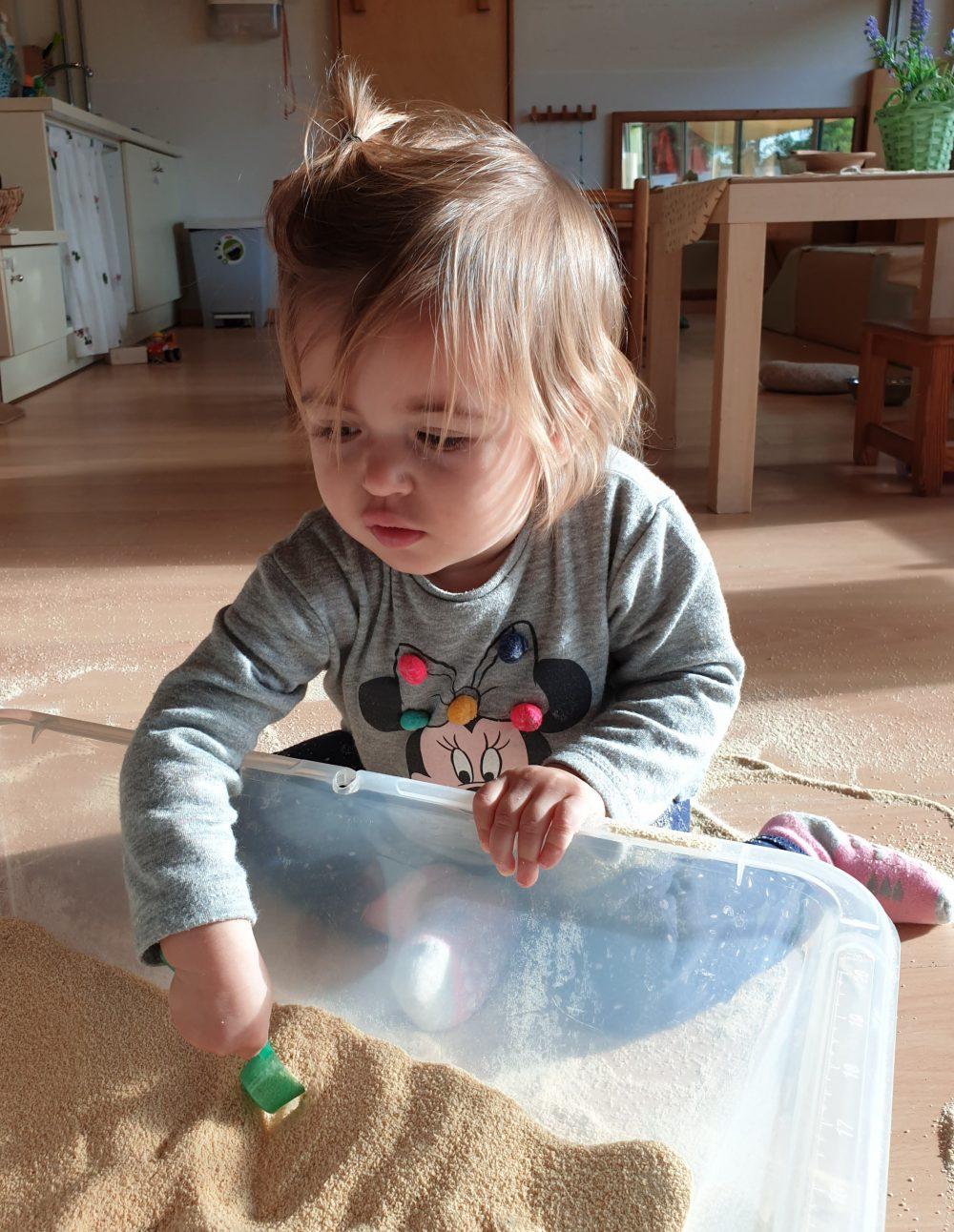 nena jugant amb pa ratllat i una cullereta