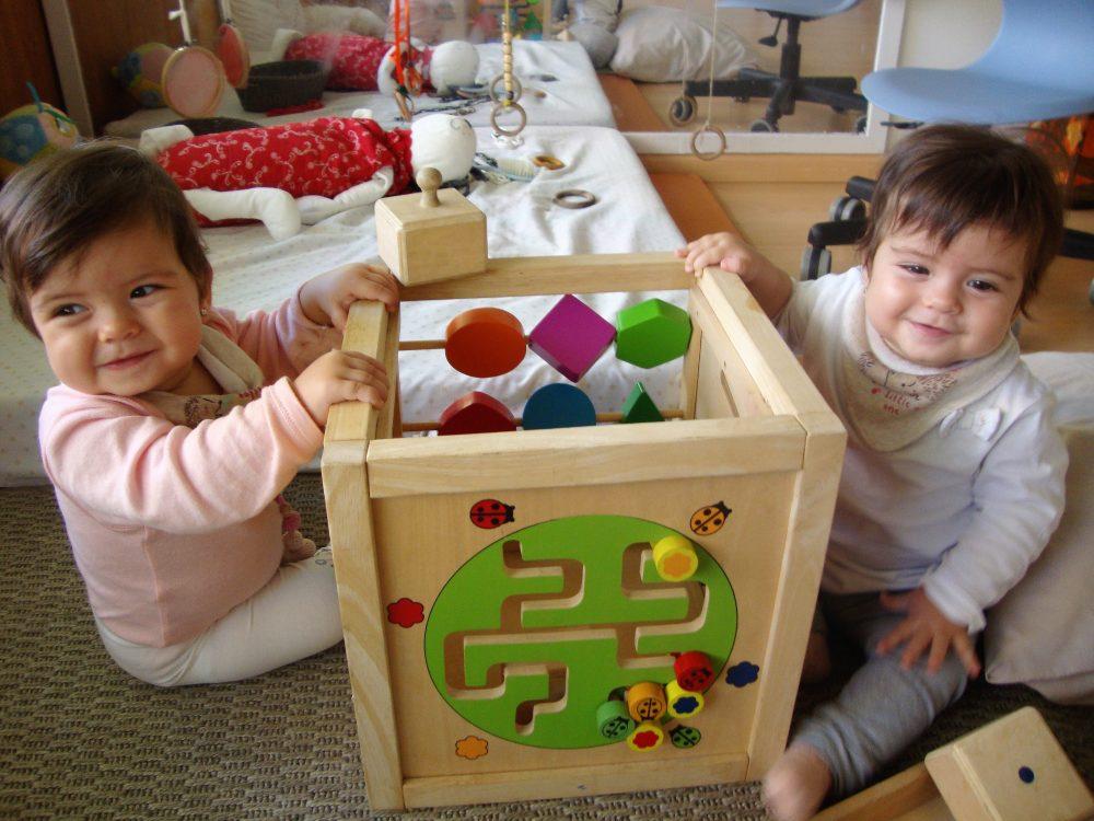 Dues nenes somriuen davant d'un cub de fusta