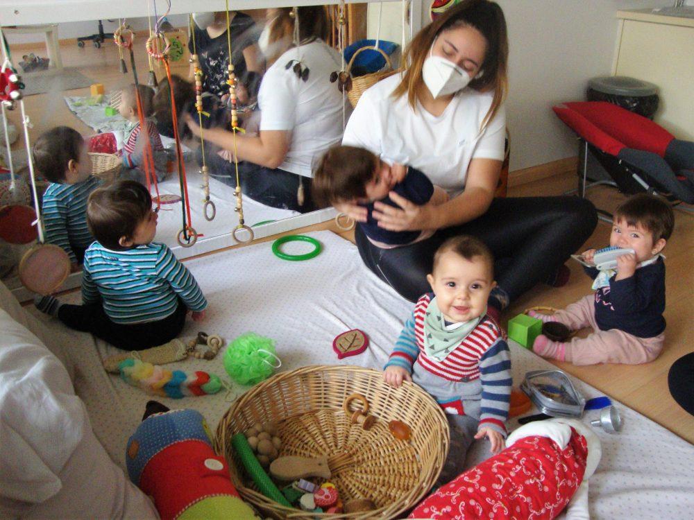 Un grup d'infants juguen a la panera dels tresors en un matalàs, amb una educadora fent un joc de falda amb una nena