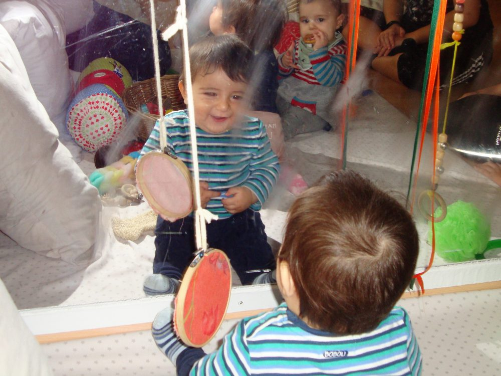 Infants mirant-se al mirall i somrient