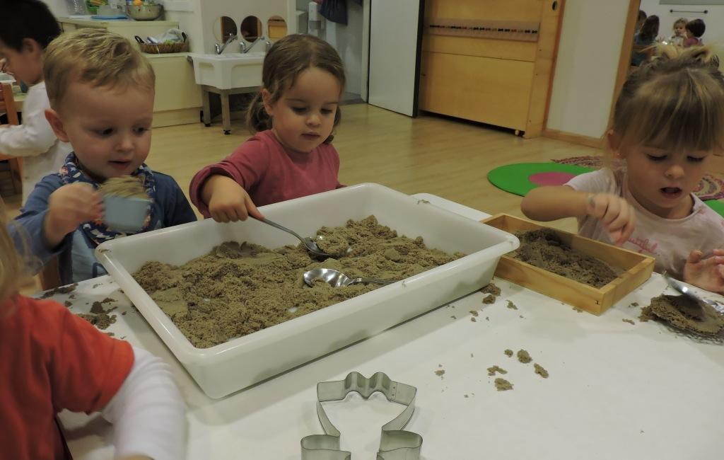 tres nens i nenes jugant amb sorra