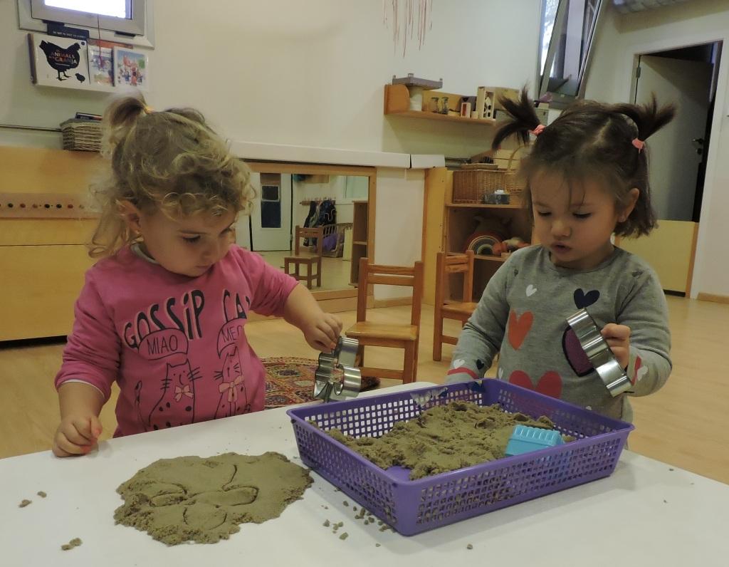 dos nenas jugant amb sorra
