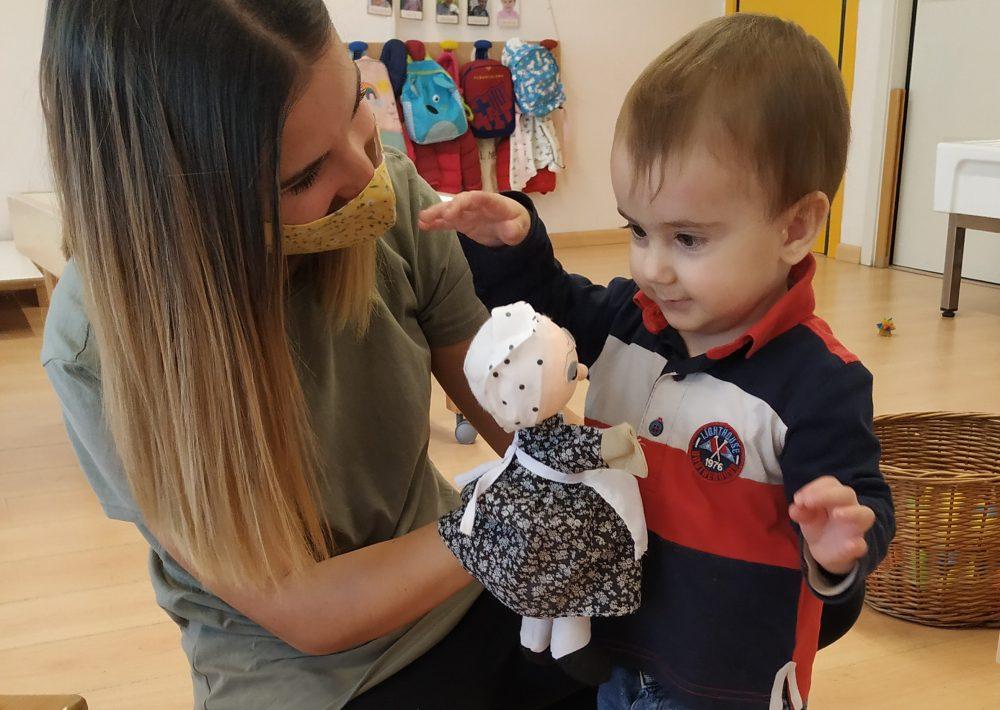 Una mestra mostra una titella de castanyera a un infant