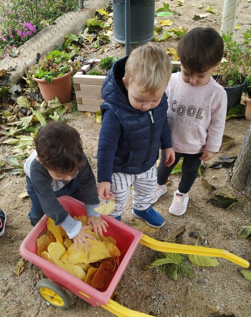 Infants recullen al pati fulles de la tardor