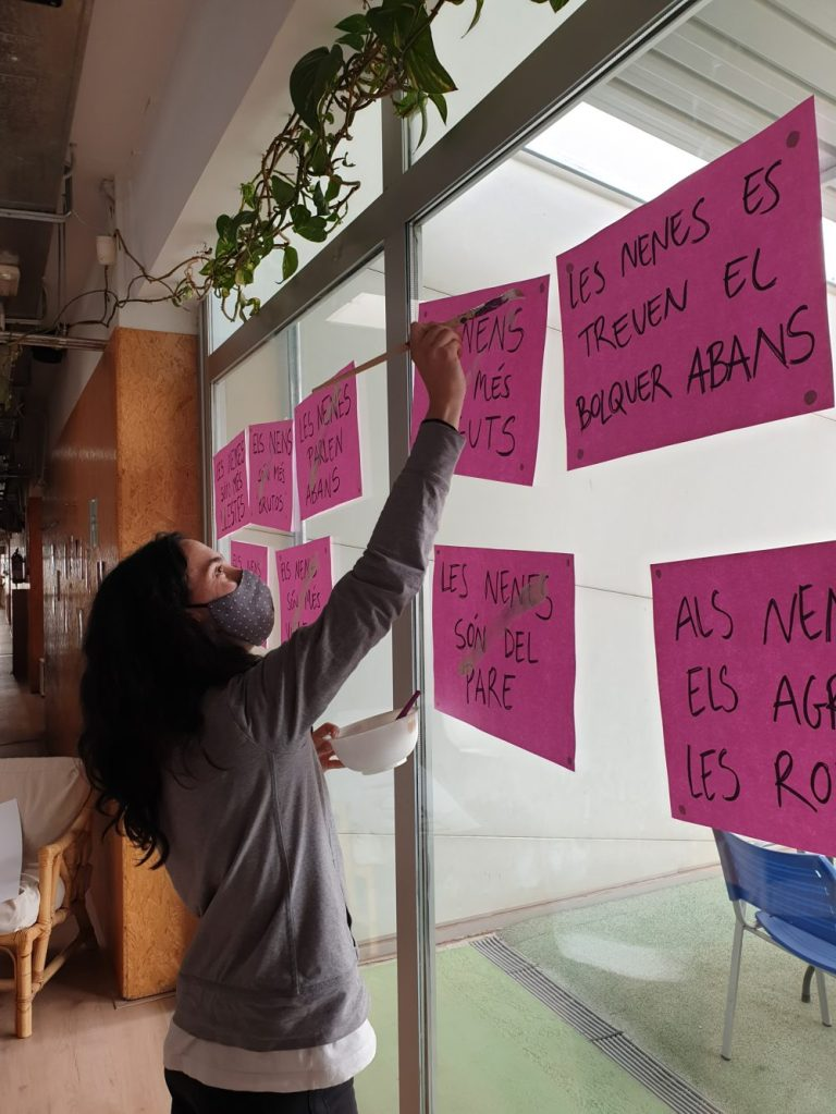 una educadora pinta els cartells que hem fet en equip