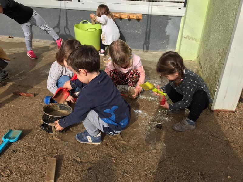 Infants jugant amb la sorra i aigua dels bassals