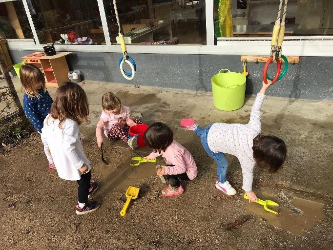 cinc infants jugant amb sorra i aigua dels bassals